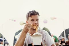 Stylish hipster man eating wok noodles with vegetables from carton box with bamboo chopsticks. Asian Street food festival. Guy royalty free stock image