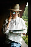 Stylish hipster man holding map and looking front view, sitting Stock Photography
