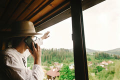 Stylish hipster  man holding phone and talking  at window with a Royalty Free Stock Photography