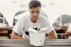 Stylish hipster man looking at wok noodles with vegetables in carton box with bamboo chopsticks. Asian Street food festival. Thai. Noodles in takeaway paper box royalty free stock photo