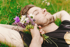 Stylish hipster man  lying on sunny grass in meadow and relaxing Royalty Free Stock Photo