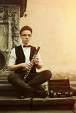 Stylish hipster man playing clarinet on background of old city s Royalty Free Stock Image