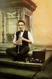 Stylish hipster man playing clarinet on background of old city s Royalty Free Stock Images