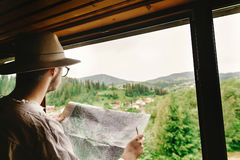 Stylish hipster man sitting at window and holding map and explor Stock Photo