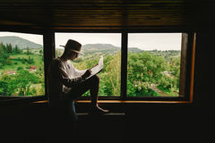Stylish hipster man sitting at window with view on mountains and Royalty Free Stock Photos