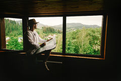 Stylish hipster man sitting at window with view on mountains and Royalty Free Stock Image
