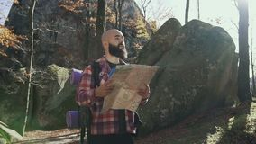 Stylish hipster man traveler with backpack holding map and exploring on top of mountains, travel concept. Autumn. A stock video