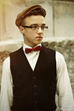 Stylish hipster man wearing glasses and tweed hat, being confide Royalty Free Stock Image