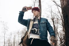Stylish hipster traveler with backpack holding smartphone and ta. King picture in winter snowy forest. wanderlust and adventure concept with space for text Royalty Free Stock Images
