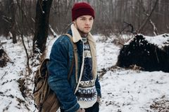 Stylish hipster traveler with backpack posing in cool sweater an Stock Photo