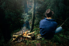 Stylish hipster traveler camping in sunny forest in the mountain Stock Photo