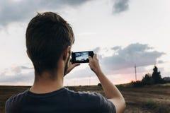 stylish hipster traveler holding smart phone taking photo of beautiful sunset landscape in summer field. instagram photography. e stock photo