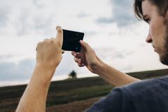 stylish hipster traveler holding smart phone taking photo of beautiful sunset landscape in summer field. instagram photography. e stock image