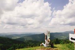 Stylish hipster traveler man falling and loosing map at top of m Royalty Free Stock Image