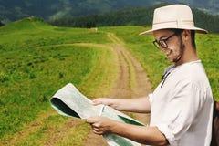 Stylish hipster traveler man holding map and smiling closeup at Royalty Free Stock Photo