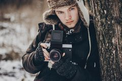 Stylish hipster traveler man with old photo camera exploring in. Snowy woods in winter. bearded guy portrait in cold forest. space for text. atmospheric moment Royalty Free Stock Image
