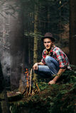 Stylish hipster traveler starting fire in sunny forest in the mo. Untains royalty free stock photo