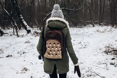 Stylish hipster traveler woman with backpack walking in winter s. Nowy forest, back view. wanderlust and adventure concept with space for text. atmospheric Royalty Free Stock Image