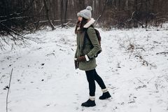 Stylish hipster traveler woman with backpack walking in winter s. Nowy forest trees with photo camera. wanderlust and adventure concept with space for text Royalty Free Stock Photography