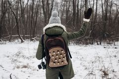 Stylish hipster traveler woman with backpack walking in winter s. Nowy forest, waving hand. back view. wanderlust and adventure concept with space for text Royalty Free Stock Photography