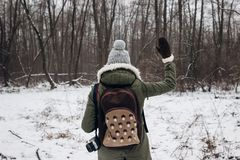 Stylish hipster traveler woman with backpack walking in winter s. Nowy forest, waving hand. back view. wanderlust and adventure concept with space for text Royalty Free Stock Photos