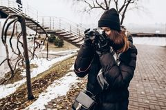 Stylish hipster traveler woman holding photo camera and taking p. Icture in winter city street. space for text royalty free stock image