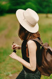 Stylish hipster woman with backpack and in hat holding sunglasse Stock Photo