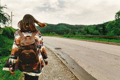 Stylish hipster woman with backpak walking and looking at mounta. Ins, summer travel concept, space for text royalty free stock photo