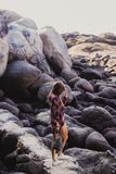Stylish hipster woman in checkered shirt and shirts on summer beach at sunset. Path in a rocks at beach Stock Photography