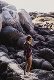Stylish hipster woman in checkered shirt and shirts on summer beach at sunset. Path in a rocks at beach Royalty Free Stock Photography