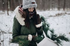 Stylish hipster woman gathering and holding pine green branches. In cloth bag. christmas tree in winter forest, atmospheric moment. festive mood. space for text Stock Image