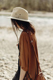 Stylish hipster woman in hat, fringe poncho walking on river beach. boho traveler girl in gypsy look, summer travel. atmospheric. Moment. space for text royalty free stock photography