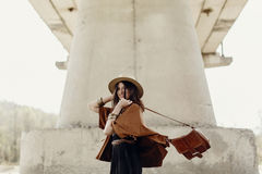 Stylish hipster woman having fun, in hat with windy hair near ri. Ver stones. boho traveler girl in gypsy look dancing with bag. summer travel. atmospheric royalty free stock photo