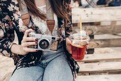 Stylish hipster woman holding lemonade and old photo camera. boho girl in denim and bohemian clothes, holding cocktail sitting on. Wooden bench at street food stock photos