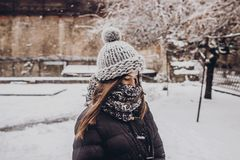 Stylish hipster woman in knitted hat standing in snowy city stre Royalty Free Stock Photography