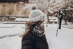 Stylish hipster woman in knitted hat standing in snowy city stre. Et. beautiful fashionable girl in warm clothes in cold snow weather with wind. space for text Royalty Free Stock Photos