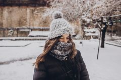 Stylish hipster woman in knitted hat standing in snowy city stre Stock Image