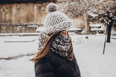 Stylish hipster woman in knitted hat standing in snowy city stre Stock Images
