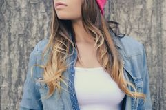 Stylish hipster woman with long hair in jeans clothing and pink hat, in white t-shirt standing against concrete wall on the street Royalty Free Stock Images