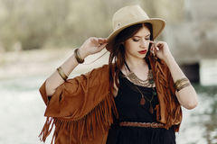 Stylish hipster woman posing in hat with windy hair, in fringe p. Oncho and accessory. boho traveler girl in gypsy look. summer travel. atmospheric moment. space stock photos