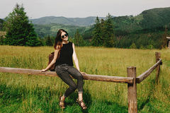 Stylish hipster woman sitting and smiling at mountains view, sum. Mer travel concept, space for text, relaxing moment Stock Images