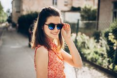 Stylish hipster woman smiling in sunglasses and enjoying sunshin. E in sunny street in summer. young girl posing and laughing. space for text. joyful moment stock image