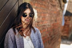 Stylish hipster woman smiling with windy hair at brick rustic wa. Ll in sunny park. young girl with sunglasses smiles in botanical garden in spring. space for royalty free stock images
