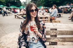 Stylish hipster woman in sunglasses with lemonade, smiling. boho girl in denim and bohemian clothes, holding cocktail sitting on. Wooden bench at street food stock photography