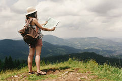 Stylish hipster woman traveler with backpack holding map and exp Stock Photography