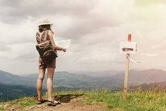 Stylish hipster woman traveler with backpack holding map and exp Royalty Free Stock Image