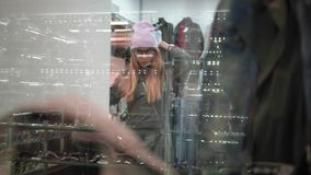 A stylish hipster woman trying on stylish clothes in the store. View through the window. Shopping.  stock video