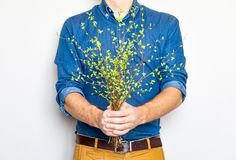 Man holding a bunch of green spring branches. Bright stylish photo, eco and love concept stock photography