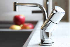 Stylish home interior sink tap and red apples Royalty Free Stock Images
