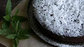 Stylish homemade baked chocolate brownie cake generously powdered with an icing sugar next to fresh mint leaves. Stylish homemade baked chocolate brownie cake stock video